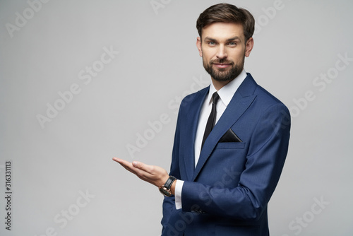 Fototapeta Portrait of a young businessman pointing on a copyspace with his finger obraz