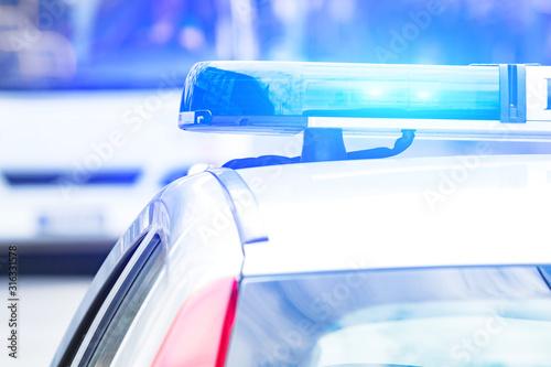 Fototapeta Police car with blue lights on the crime scene in traffic / urban environment. obraz