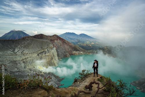 Spectacular view of female hiker standing in Mount Ijen volcano on East Java wit Wallpaper Mural