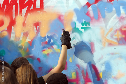 young people draw graffiti on the wall of the building - 316334711