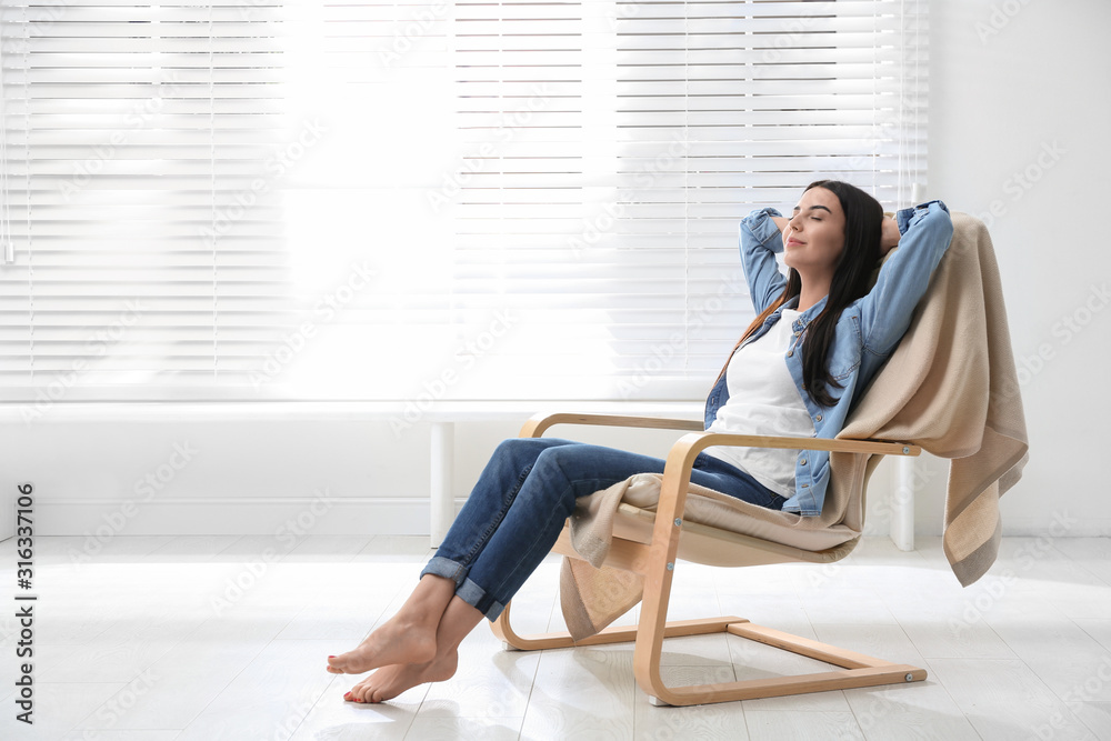 Fototapeta Young woman relaxing in armchair near window at home