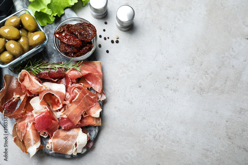 Obraz Tasty prosciutto served on light grey table, flat lay. Space for text - fototapety do salonu