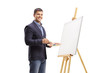 canvas print picture - Young man painting on a canvas and smiling at the camera