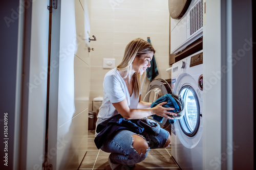 Fototapeta Smiling caucasian blond worthy housewife dressed casual crouching in bathroom and loading washing machine with dirty clothes in late hours. obraz