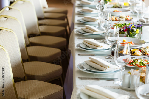 Fototapeta Serving banquet table in a restaurant. White napkins, wine glasses, vegan snacks, beige chairs in a row obraz