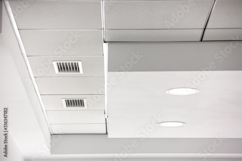Canvas Print multi-level gypsum plasterboard ceiling and a white square tile suspended ceiling with integrated lighting lamps and ventilation grilles, close up details