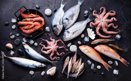 Photo Fresh fish and seafood assortment on black slate background