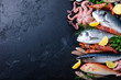 canvas print picture - Fresh raw fish and seafood assortment on black slate background. Top view. Copy space.