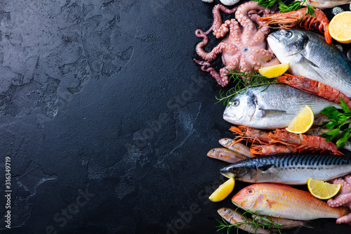 Fresh raw fish and seafood assortment on black slate background Fototapete