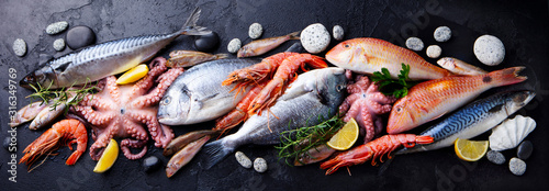 Fresh fish and seafood assortment on black slate background. Top view. - 316349769