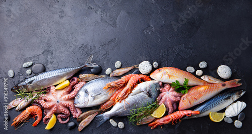 Fototapeta Fresh fish and seafood assortment on black slate background. Copy space. Top view. obraz
