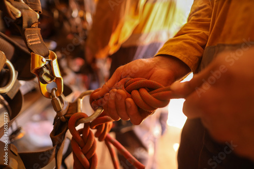 Fototapety, obrazy: Rope access technicians double checking inspecting gear figure of eight knot 10.5 mm static rope call as cawtails after tie into abseiling safety harness loop prior working of each task