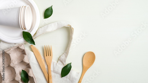 Fototapeta Eco friendly cotton bag, bamboo cutlery set, biodegradable paper utensils, egg carton and green leaves. Zero waste, plastic free concept. Sustainable lifestyle obraz