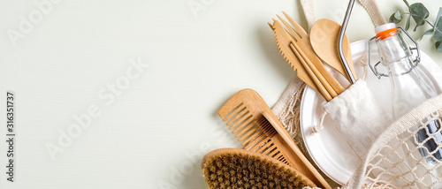 Fotografie, Tablou Set of eco friendly bamboo cutlery, mesh shopping bag, massage brush, glass bottle, bamboo toothbrush, wooden hair comb