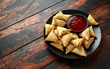Fresh Indian Samosa with dipping sweet chili sauce on wooden table