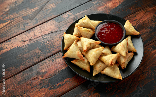 Fresh Indian Samosa with dipping sweet chili sauce on wooden table Wallpaper Mural