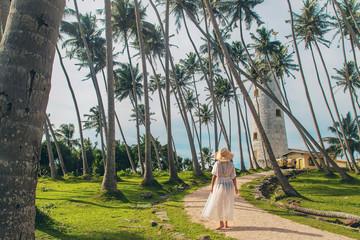Girl in Sri Lanka on an island with a lighthouse. Selective focus.