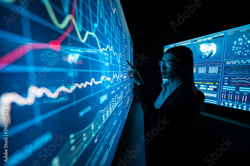 The business lady standing near the sensor screen in the dark laboratory