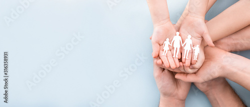 Fototapeta Family care concept. Hands with paper silhouette on table. obraz