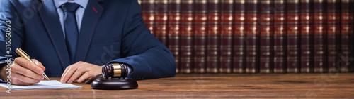 Fotografie, Obraz Lawyer Signing Documents Near Mallet