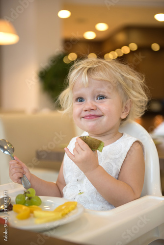 happy little caucasian girl eating fruits indoors at home healthy eating #316362971