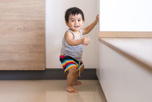 Cute Active Asian Little Baby Boy Is Standing On The Floor And Trying Begin To Walk For First Step Himself, Concept Of Learning And Developing Of Child In The First Year Of Life.