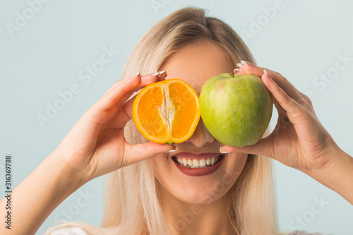Photo beautiful young woman with green apple and orange in hands on a blue background