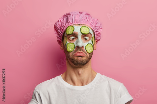 Foto Young man crosses eyes, applies cream mask on face with cucumber, has beauty session, wears bath cap, reduces dark dotes on complexion, isolated over pink background