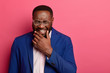Leinwanddruck Bild - Photo of overjoyed Afro American man laughs at funny story, cant stop giggling, has white teeth, thick beard, wears formal suit, squints face, isolated on pink background, glad to achieve success