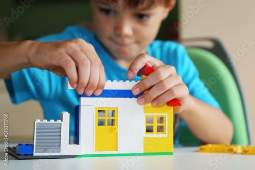 Photo Junge baut mit Bausteinen ein Haus