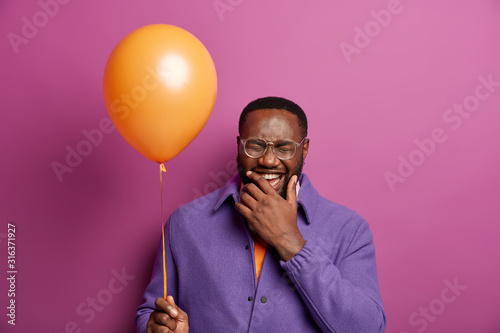 Crazy positive man laughs out from happy emotions, has fun time, poses with bright inflated balloon, holds chin, wears purple jacket, ready for celebration, hears funny anecdote from friend Wallpaper Mural
