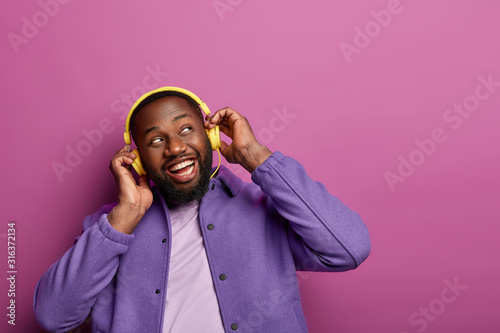 Fotografía Horizontal view of positive guy wears stereo headphones on ears, enjoys live music, looks aside, being music meloman, dressed casually, has hobby, isolated over vivid studio wall
