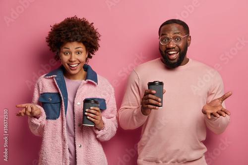 Happy dark skinned girlfriend and boyfriend drink caffeine beverage, hold paper Canvas Print