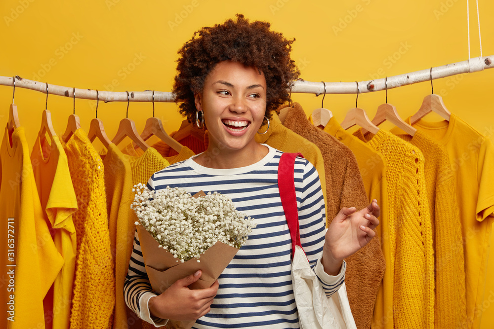 Fototapeta Positive curly haired woman in striped jumper, stands with bouquet and shopping bag, returns from store, refreshed her wardrobe with yellow clothes, has happy mood after successful purchasing