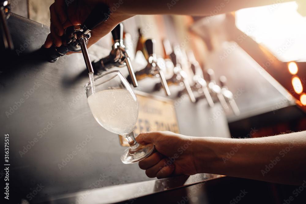 Fototapeta Barman pours light alcoholic cider of keg tap into glass. Dark background
