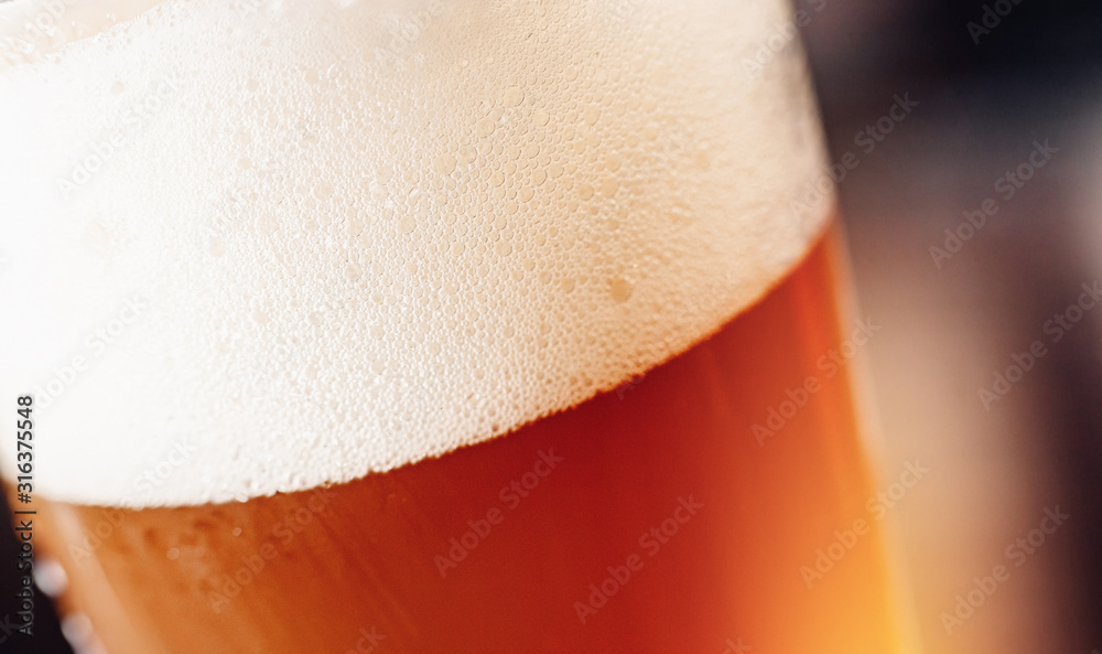 Fototapeta Gold background texture of yellow light beer with froth and bubbles in glass, copy space