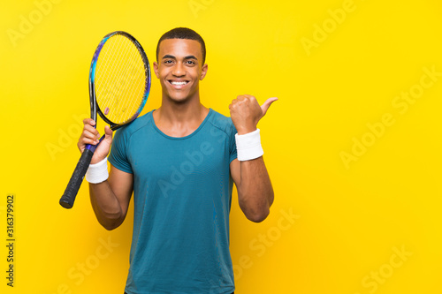 Fotografija African American tennis player man pointing to the side to present a product