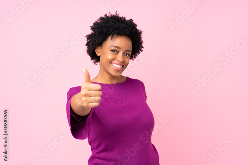 African american woman over isolated pink background with thumbs up because something good has happened
