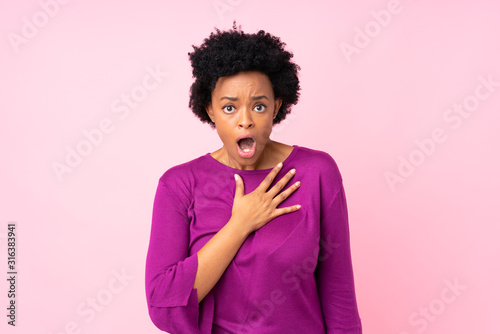 Fotografia, Obraz African american woman over isolated pink background surprised and shocked while