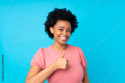 Fototapeta African american woman over isolated blue background giving a thumbs up gesture obraz