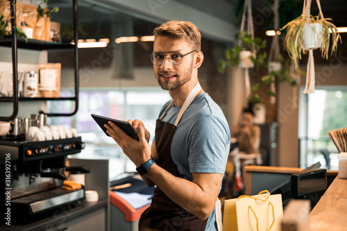 Tela Smiling male cafe owner holding digital tablet in his hand