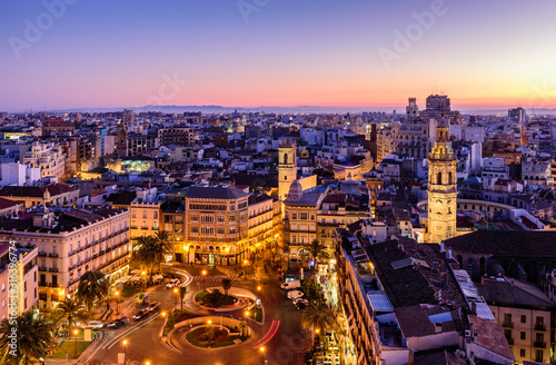 Sightseeing of Spain. Aerial view of Valencia at sunset. Illuminated Plaza de la Reina, cityscape of Valencia.