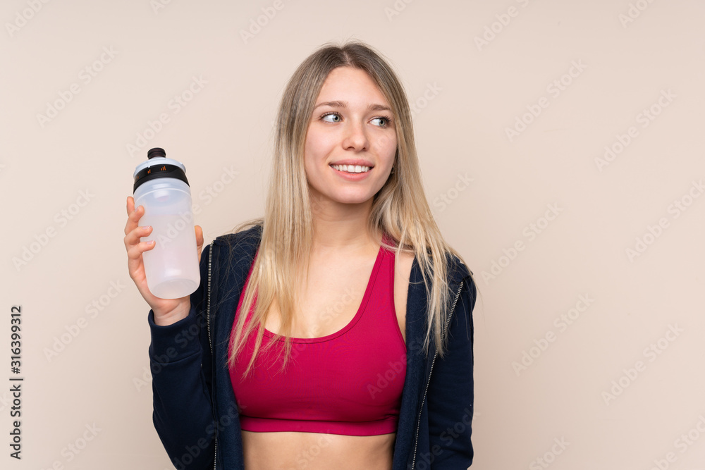 Fototapeta Young sport blonde woman over isolated background with sports water bottle