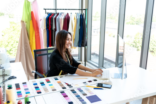 Fényképezés Happy smiling Asian creative fashion designer is working owner working in her tailor shop