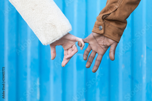 Photo Arms of interracial couple holding hands, great love symbolic concept, blue background