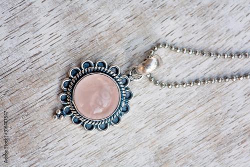 Silver pendant on neutral bright wooden background Fototapeta