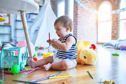 Obraz Adorable toddler playing around lots of toys at kindergarten - fototapety do salonu