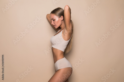 Young woman in beige underwear on beige background Canvas Print
