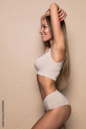Obraz Young sexy woman with perfect body in underwear standing on beige background - fototapety do salonu