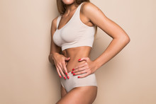 Young Woman In Beige Underwear On Beige Background. Fitness, Diet, Skin And Body Care